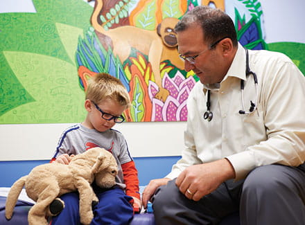 James Geller, MD, takes a moment to play with a 3-year-old cancer patient, Carson, during a clinic visit.