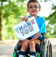 Patient in wheelchair holding a thank you sign.