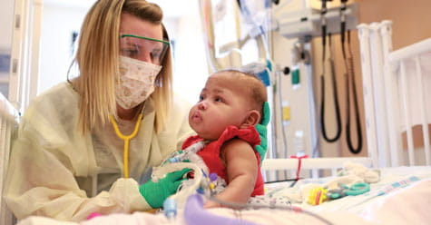 Nurse and baby in NICU.