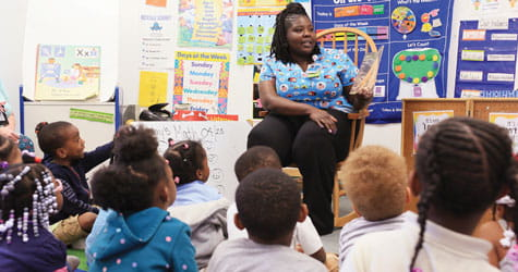 Cincinnati Children's employee reads to school children.