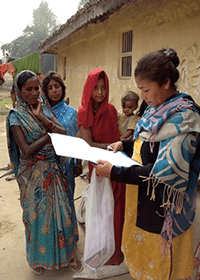 A researcher surveys villagers in Nepal.