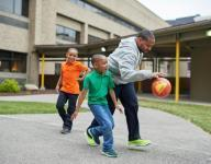 A father and two young boys play with a ball.