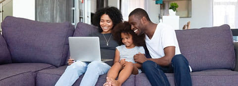 A family sitting on the couch watching a laptop screen and smiling.