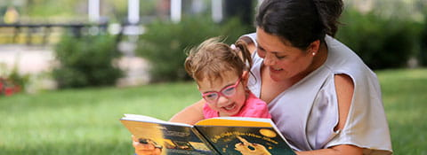 Picture of a mother and daughter reading a book outside.