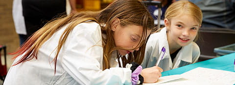 Picture of two girls wearing lab coats. One is writing something with a pen.