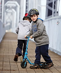 Kids wearing helmets while riding their bikes.