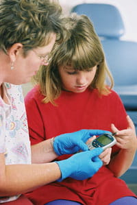 A tween monitors her blood glucose levels.