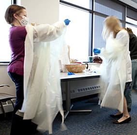 Pediatric residents racing to don protective gear.