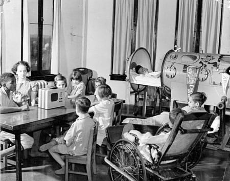Boy in iron lung joins other children in playroom.