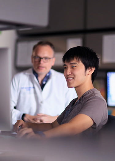 An image of Stephen Trisno and Christopher Mayhew, PhD, in the lab.