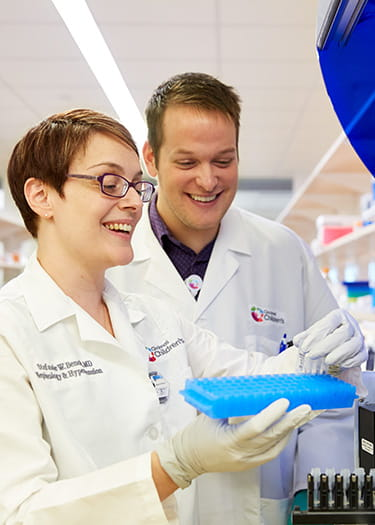 An image of Stephanie Benoit, MD, and James Rose in the lab.