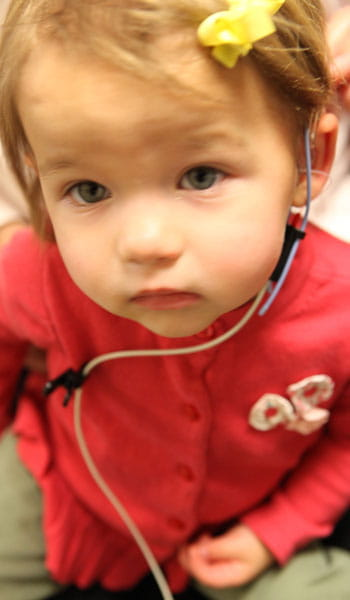 A toddler is prepared for a series of tests to ensure her hearing aids are functioning properly.