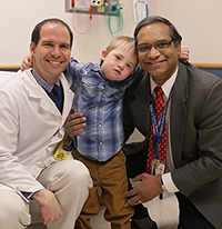 Brian A. VanderBrink, MD (left) and Pramod P. Reddy, MD (right), both from the Division of Pediatric Urology, take time to pose for a picture with a patient in the Colorectal Center clinic.