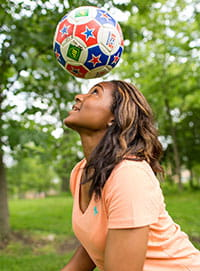 Female teen playing with a soccer ball.