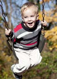 A child enjoys the swing set.