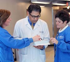 Dr. Ajay Kaul (center) consults with care coordinators Rebecca Bailey (left) and Jackie Dierig (right).