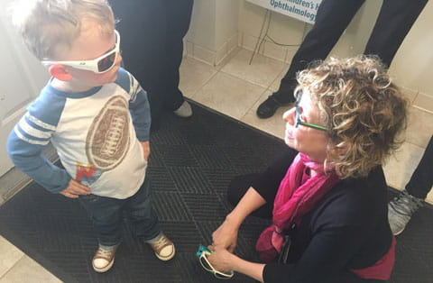 Pediatric Ophthalmologist Terry L. Schwartz, MD examines a patient's new sunglasses.
