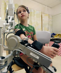 A patient uses the external support device call the Armeo®Spring Pediatric to help build strength and increase range of motion.