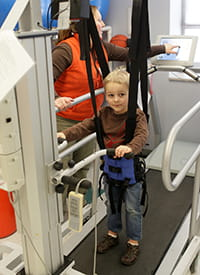 A young patient uses the LifeGait® machine.