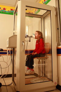 A patient performs a lung volume test while at the Pulmonary Function Laboratory.