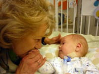 A mother kisses her child in the Transitional Care Center.