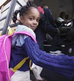 A young girl boards a school bus.