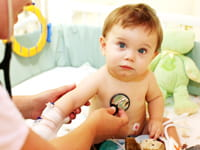 A baby is examined with a stethoscope.